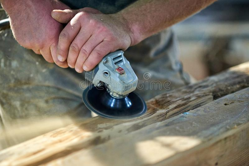 Wood grinding by carpenter stock photos