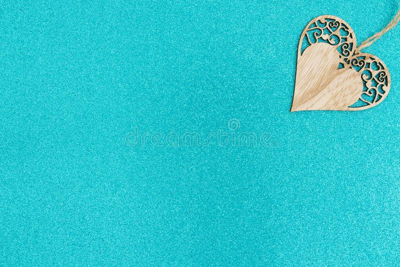 Wood heart on bright teal glitter background stock image