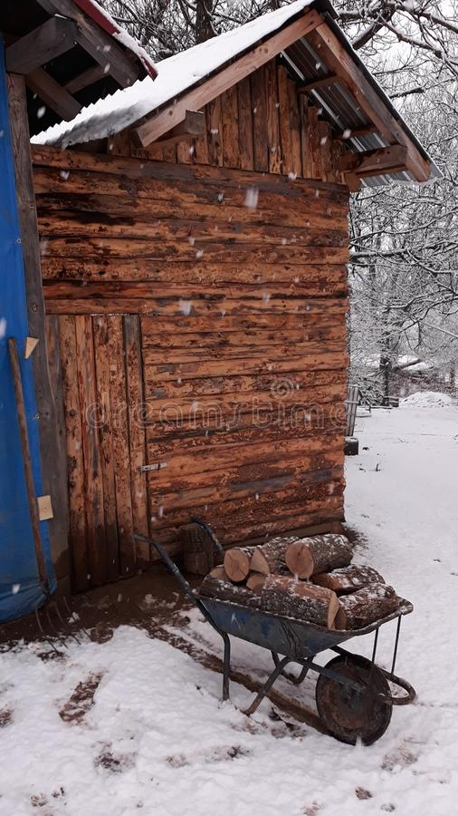 Wood house on winter snow day. Picture of Wood house on winter snow day with wood for warming royalty free stock image