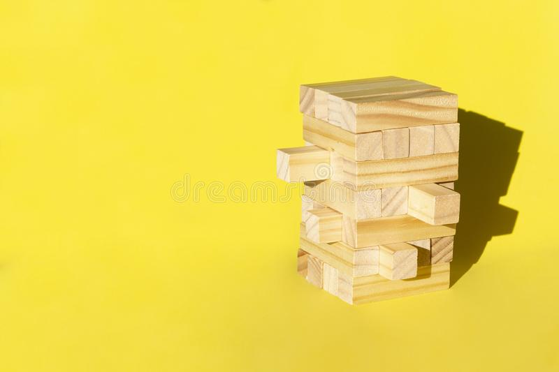 Wood jenga game with wooden block Stack tower on yellow background, manage risk and strategy royalty free stock photos