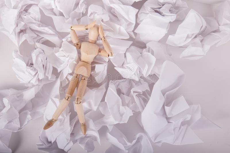 Wood jointed manikin hands on head overwelmed laying on crumbled up paper balls royalty free stock image