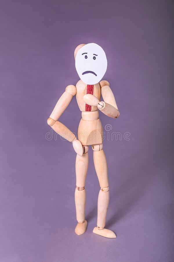 Wooden manikin standing with one hand on hip one hand holding up a sad face sign over his face stock photos