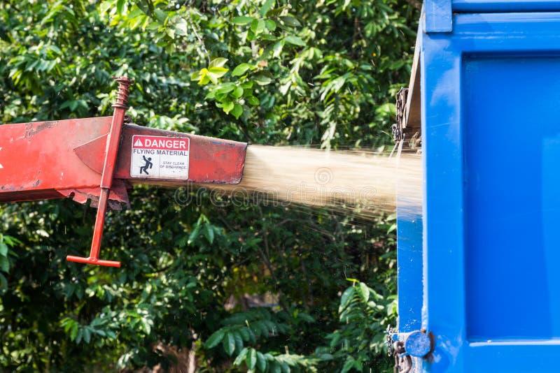 Wood käck maskin som släpper de strimlade träna in i en lastbil arkivfoto