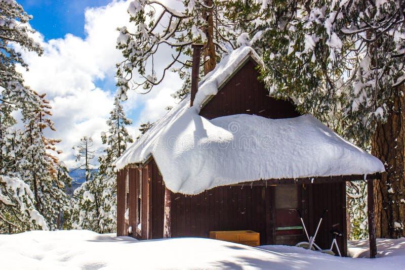 Wood kabin med snö på taket royaltyfri bild