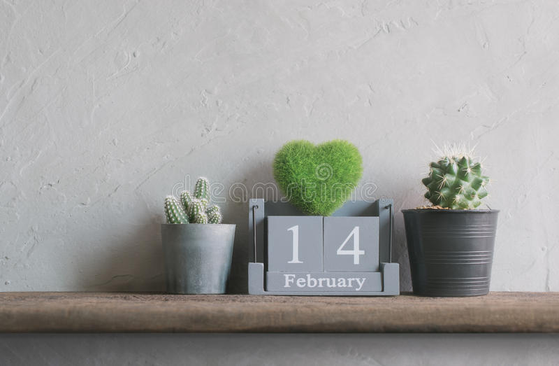 wood kalender för tappning för Februari 14 med grön hjärta på trä t royaltyfri bild
