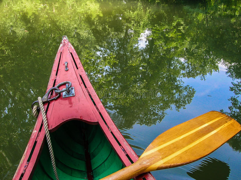 Wood kanot med reflexion av träd och himmel i vatten royaltyfri foto