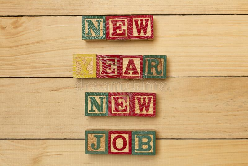 Wood kuber på trätabellen med jobb för nytt år för ord nytt kyler royaltyfri bild