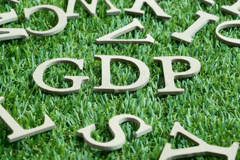Wood letter in word GDP Abbreviation from Good distribution practice or Gross domestic product on artificial green grass. Wit English alphabet background royalty free stock photography