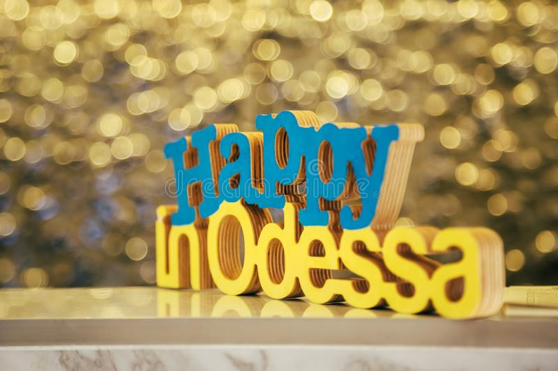 Wood letters Happy in Odessa in blue and yellow colors of the Ukrainian flag with a gold bokeh at the background.  stock image