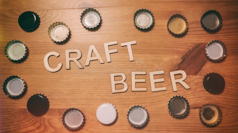 Craft Beer Wood Letters Bottle Caps. Wood letters spelling out craft beer. Bordered by beer bottle caps stock image