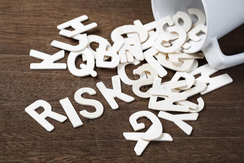 Accidental Risk Spill. Wood letters spill out of a cup as RISK word royalty free stock images