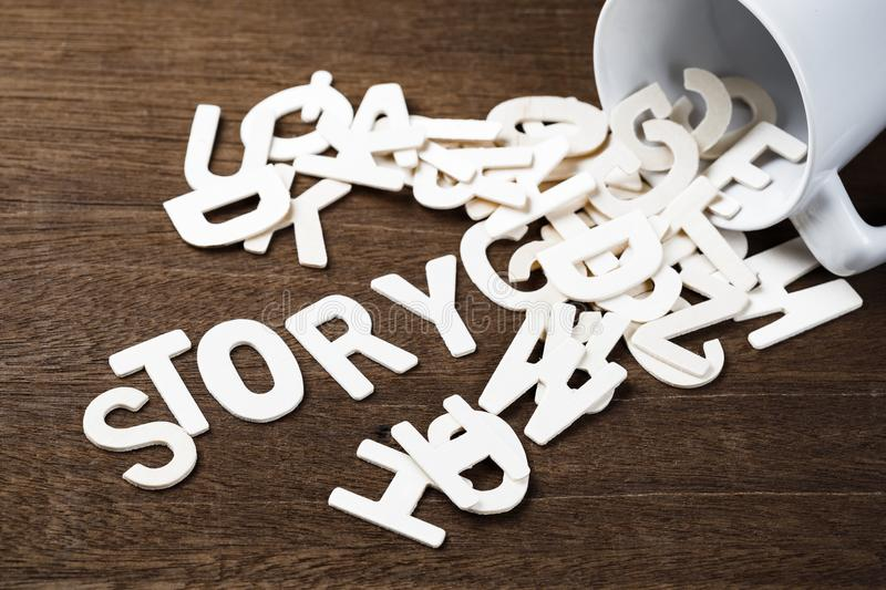 Story Spill Out. Wood letters spill out of a cup as STORY word stock photography