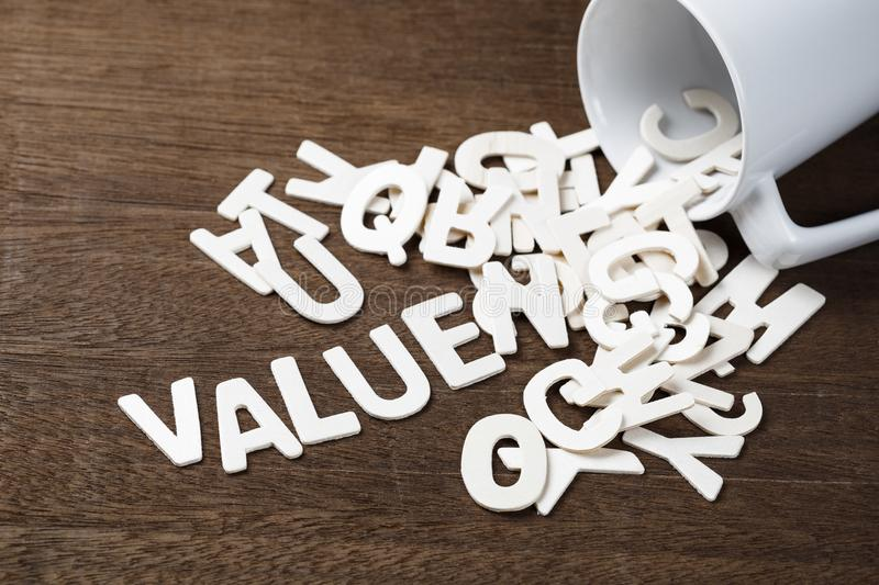 Value Spill Out. Wood letters spill out of a cup as Value word stock images