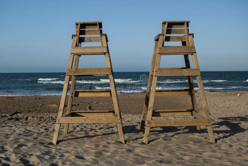 Wood lifeguard post in the beach. Sunset horizon line between sk. Y and sea stock photos