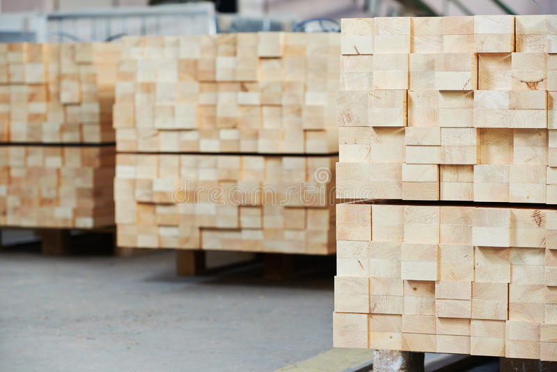Wood lumber materials at plant. Stacked wood pine timber production for processing and furniture production at woodworking enterprise royalty free stock photography