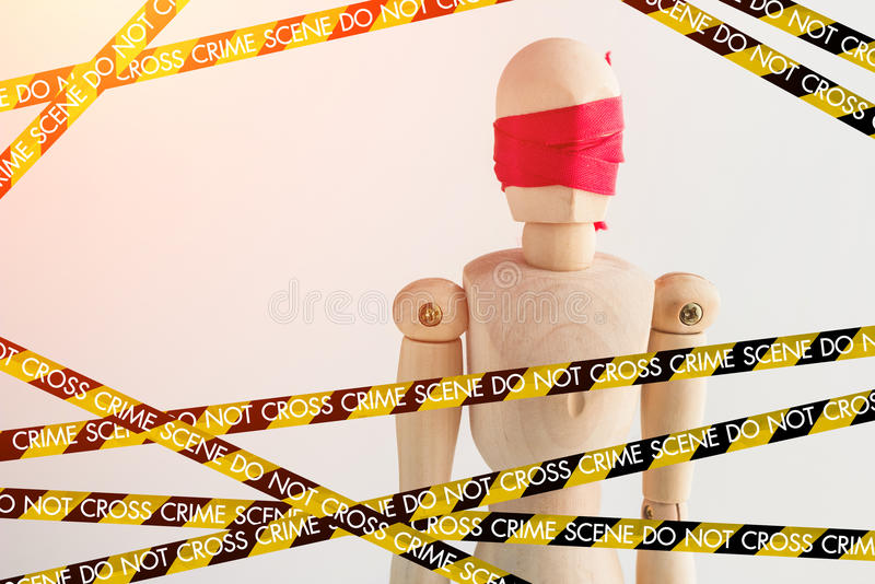 Wood man figure blind with red ribbon with police line crime scene tape. And copy space for your idea royalty free stock photo