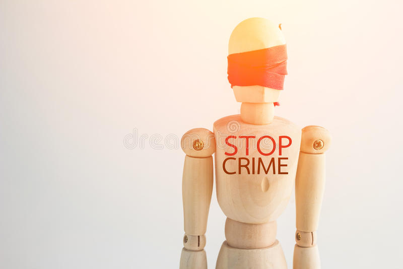 Wood man figure blind with red ribbon with word stop crime stock images