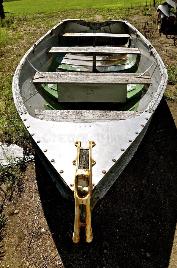 Wood and metal boat. An old weathered wood and metal boat which has been pulled out of the water royalty free stock images