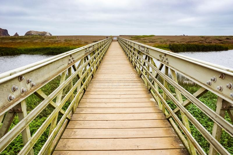 Wood and metal bridge crossing the Rodeo Lagoon towards Rodeo Beach, Headlands, Golden Gate Recreation Area, Marin County,. California royalty free stock photography