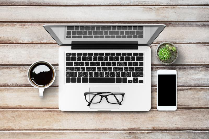 Wood office desk table with laptop, smartphone, cup of coffee and supplies. Top view with copy space, flat lay stock images