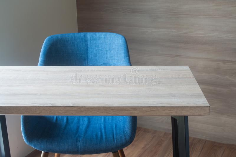 wood office table with blue chair on wood wall background texture at working room. view form front office table. stock photography