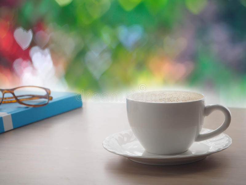 Wood office table with latte coffee cup and modern eyeglasses on blue book cover, beautiful heart shape bokeh texture background. stock photos