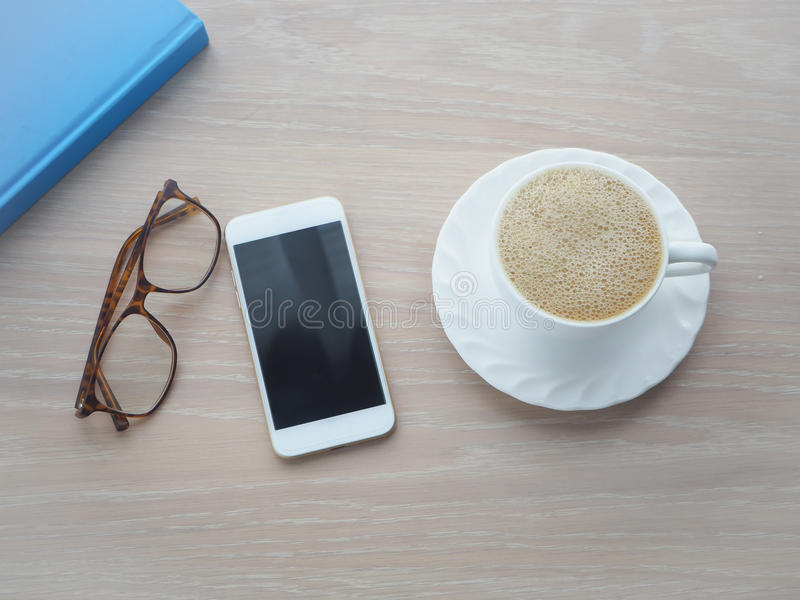 Wood office table with white coffee cup of latte coffee, blank s royalty free stock image