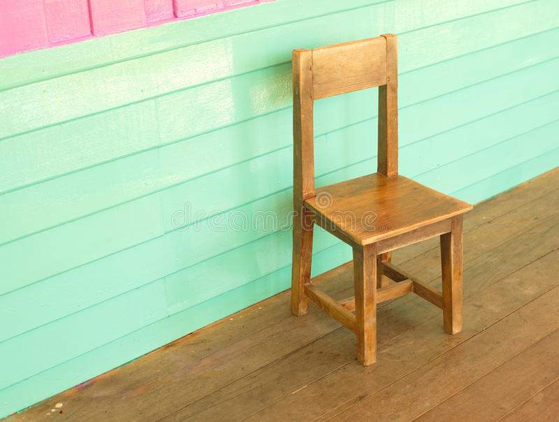 Wood old kid chair. In front of colorful pink and vintage blue wall stock image