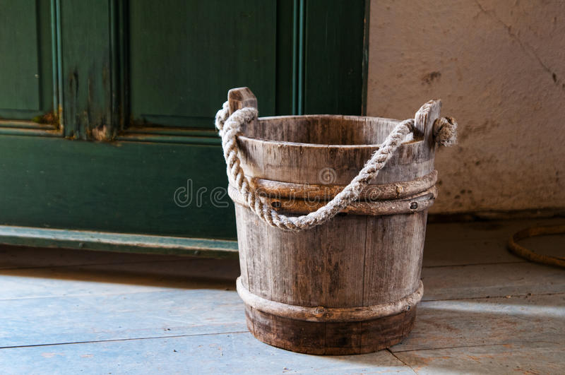Wood pail. Old fashion wooden pail by a green door stock image