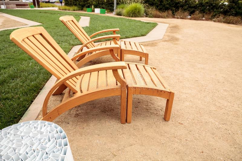 Wood patio lounge chairs in the backyard stock images