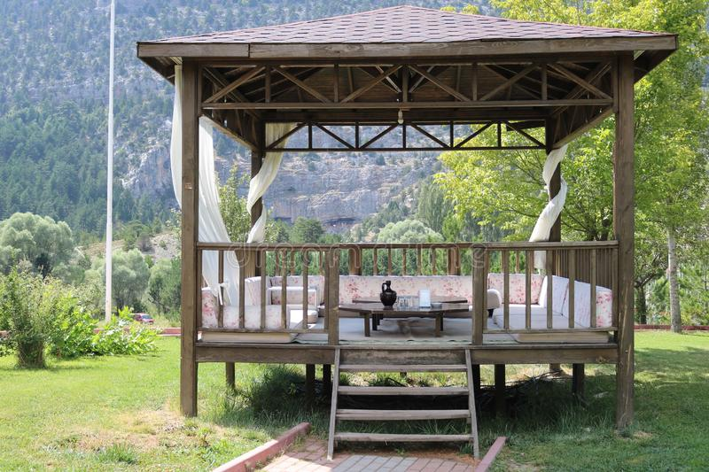 Wood pavillon. Wood pergola and forest. Wooden arbour in park a background of green lawn and trees royalty free stock photo
