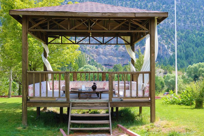 Wood pavillon. Wood pergola and forest. Wooden arbour in park a background of green lawn and trees royalty free stock images