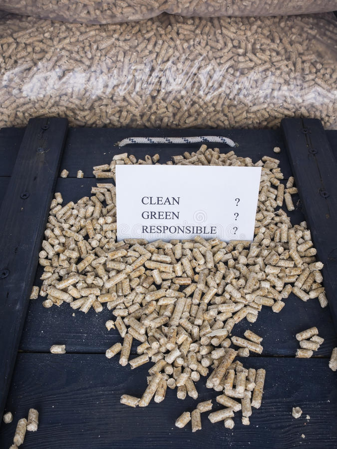 Wood pellets and check list. Wood pellets in a wood pellet store with a check list carrying the words clean, green, responsible, with question marks against each royalty free stock photo