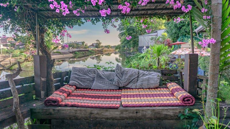 Wood pergora with ivy and mattress-pillow at riverside royalty free stock photos