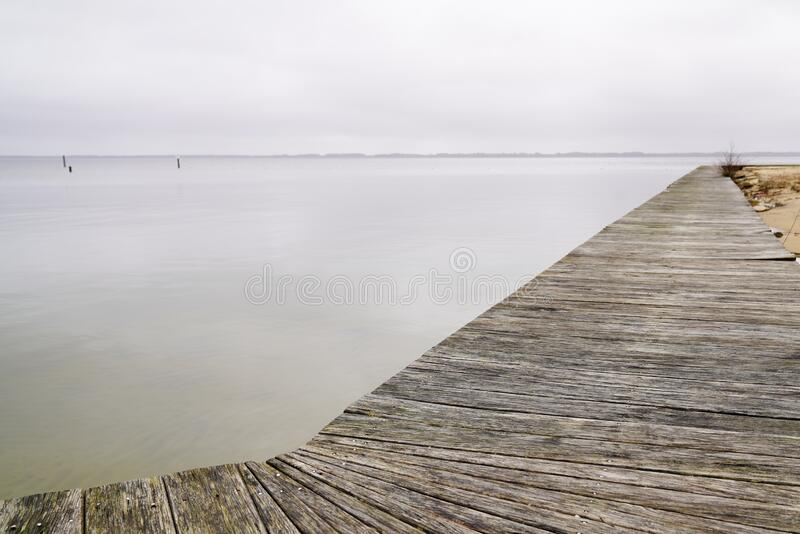 Wood pier long pontoon jetty on water Sanguinet lake in landes France. A wood pier long pontoon jetty on water Sanguinet lake in landes France royalty free stock photos