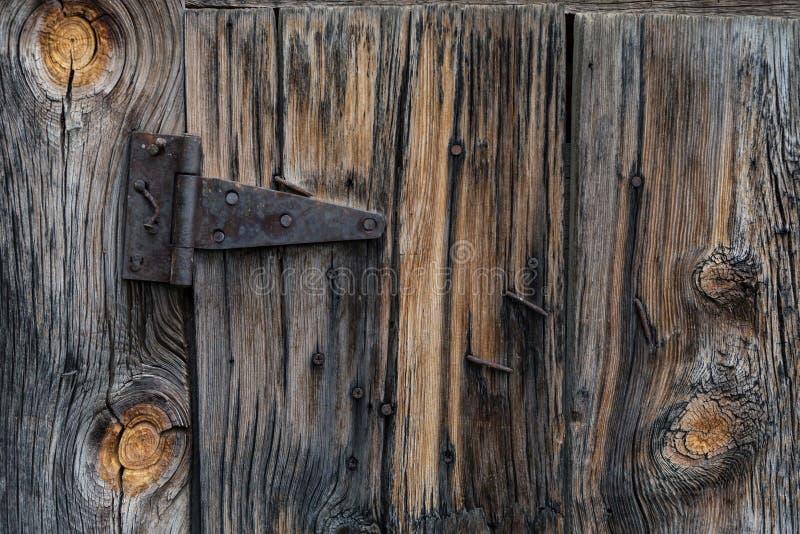 Wood plankadörr för gammal ladugård och rostigt gångjärn arkivbilder