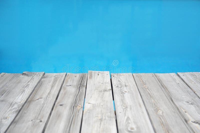 Wood plankapir mot blått vatten royaltyfria bilder