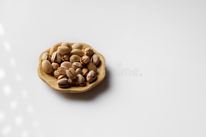 Wood plate of salted pistachio nuts royalty free stock photos