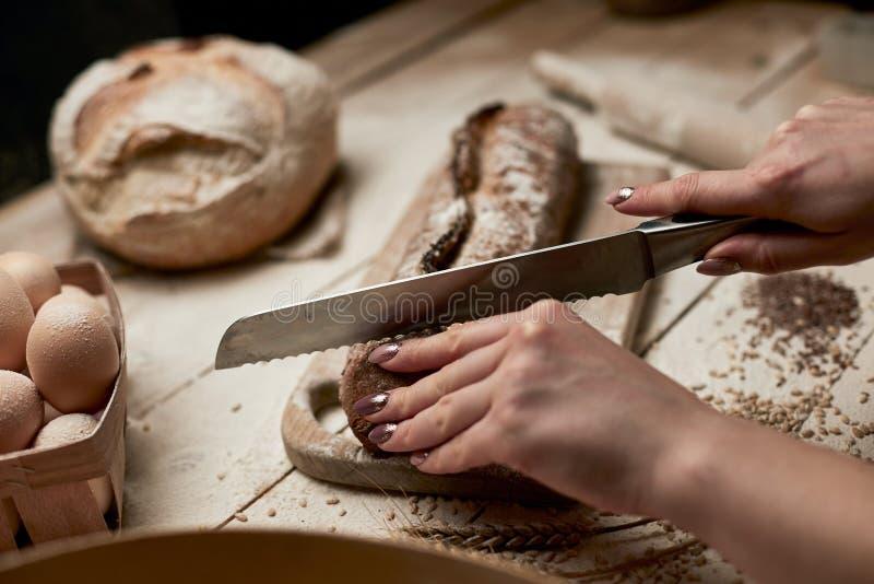 Wood platta f?r helt k?k f?r kornbr?d p?lagt med en h?llande guld- kniv f?r kock f?r snitt Nytt br?d p? tabelln?rbild Nytt bröd p fotografering för bildbyråer