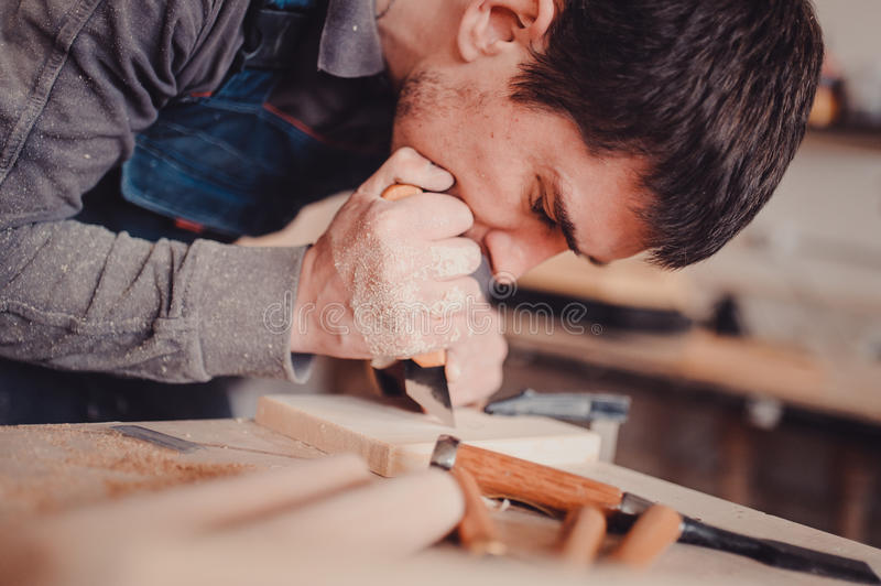 Wood processing. Joinery work. wood carving. The carpenter uses a cutting knife for framing royalty free stock images