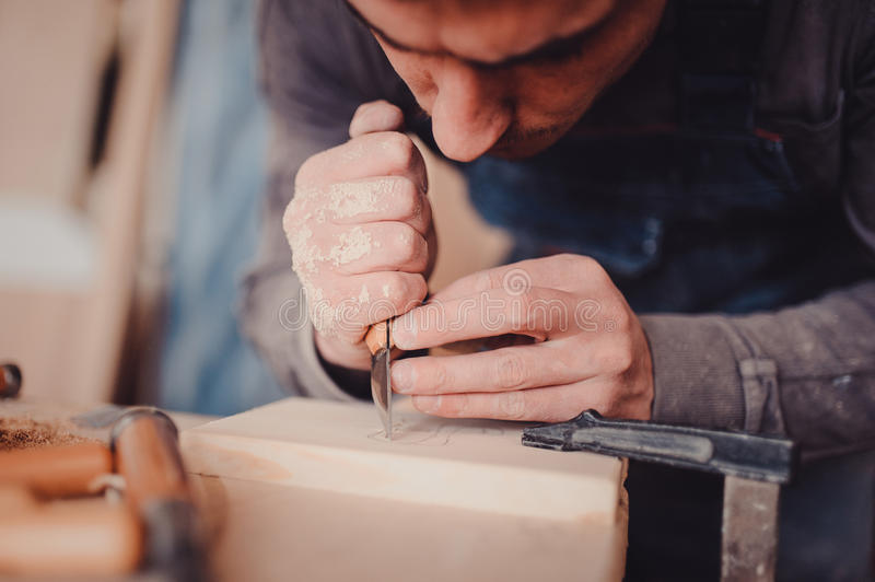 Wood processing. Joinery work. wood carving. The carpenter uses a cutting knife for framing stock images