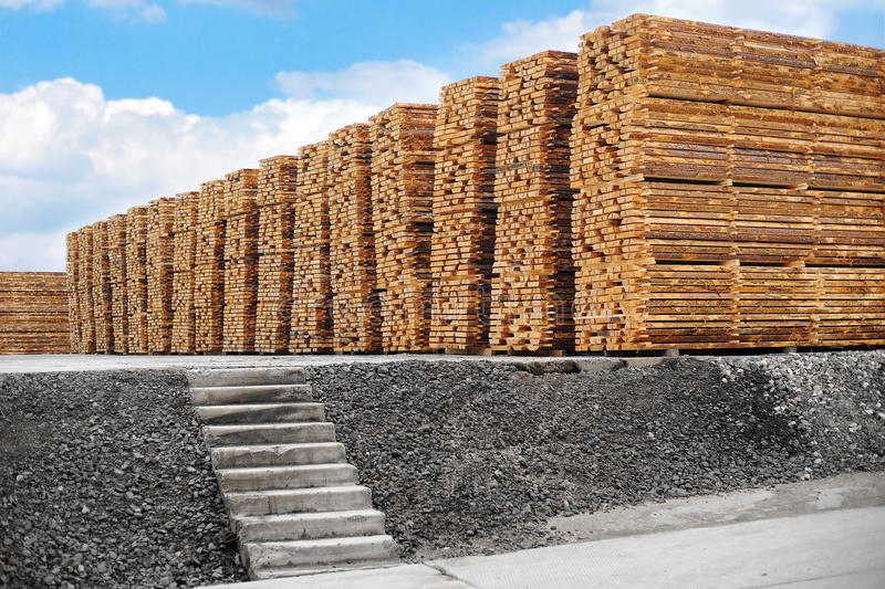 Wood processing plant. Stacked up lumber in warehouse. Outdoors. Woodworking industry royalty free stock photo