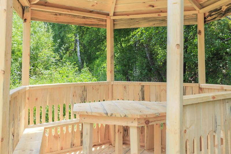 Wood products, bower. Carpentry skill. Camping, a shelter for tourists. New arbor, gazebo made of wood and a table against the. Backdrop of summer wood for stock image