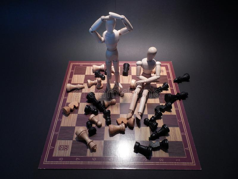 Wood puppets on chessboard stock photos
