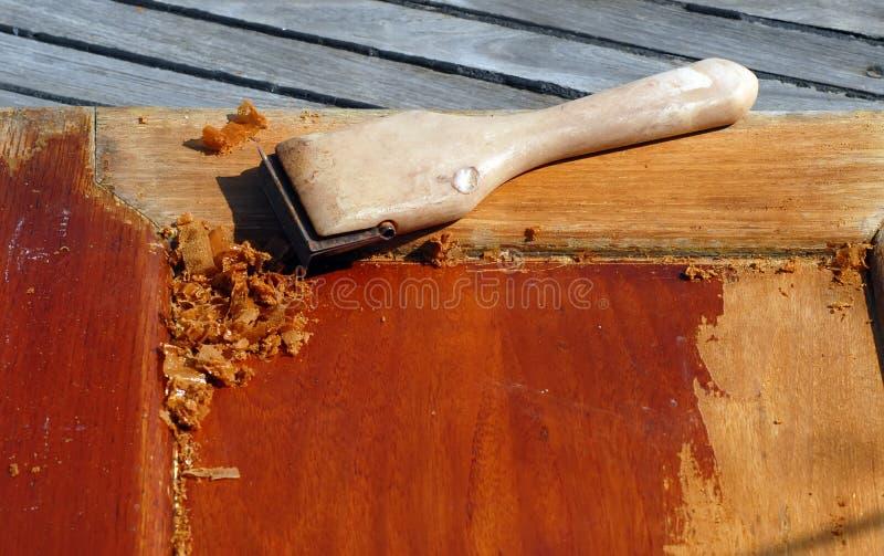 Wood refinishing. Scraper on teak wood door, old varnish being removed royalty free stock photos
