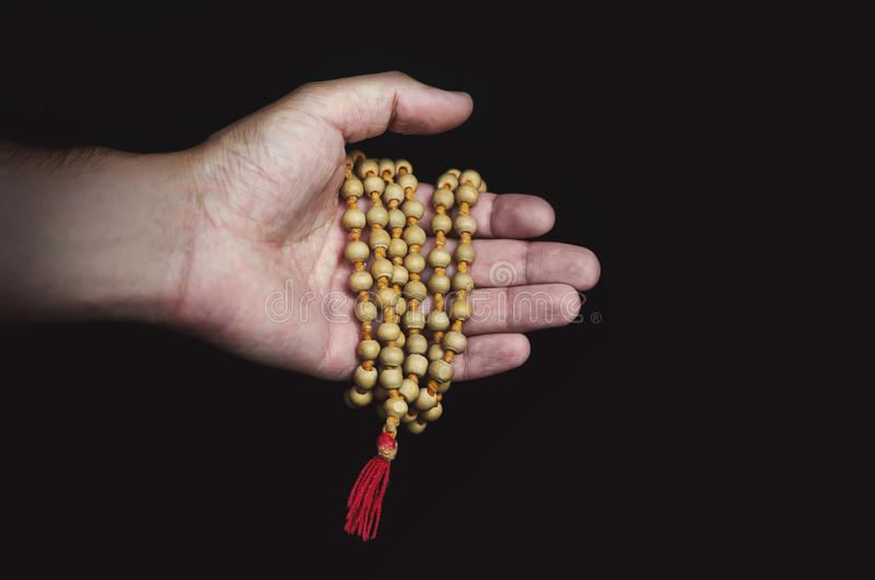 Wood sandalwood prayer beads in hand on black background royalty free stock photos