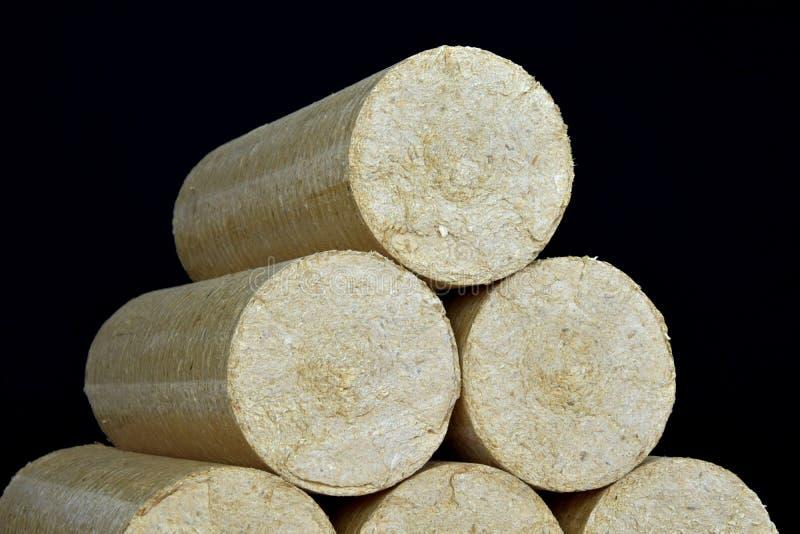Wood sawdust briquettes straightened, black background. Alternative fuel, bio fuel.  stock image