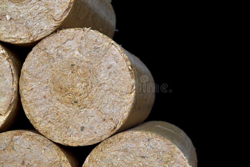 Wood sawdust briquettes straightened, black background. Alternative fuel, bio fuel.  stock photography