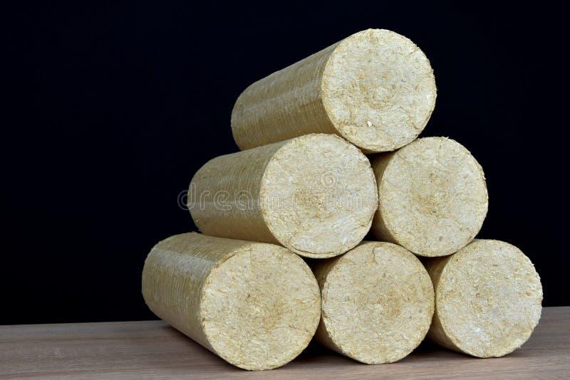 Wood sawdust briquettes straightened, black background. Alternative fuel, bio fuel. Wood sawdust briquettes straightened, black background. Alternative fuel stock photo