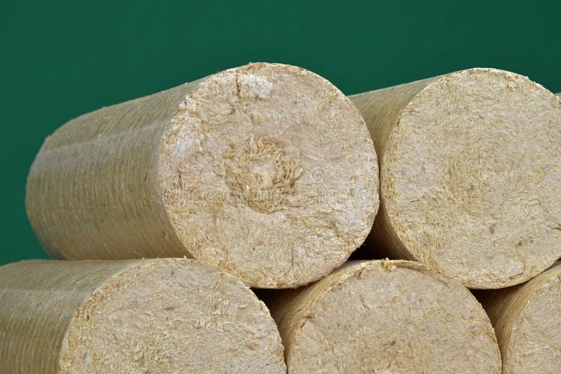 Wood sawdust briquettes straightened, green background. Alternative fuel, bio fuel.  royalty free stock photo